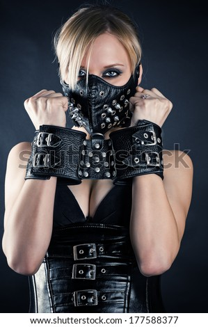 woman slave in a mask with spikes - stock photo