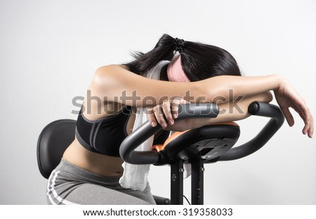 Woman sleep on exercise bike over white background - stock photo