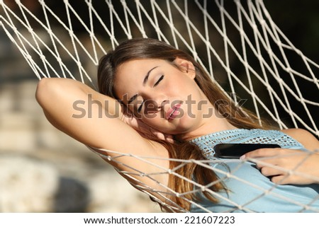 Woman sleeping and resting on a hammock with a mobile phone on the chest - stock photo
