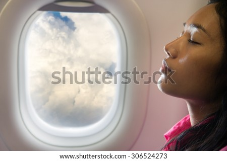 woman sleeping at air plane. Tired passenger resting at flying aircraft. Portrait of a sleeping woman dreaming in the clouds. - stock photo