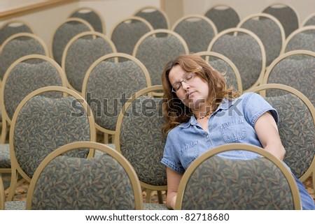 Woman sleeping at boring conference - stock photo