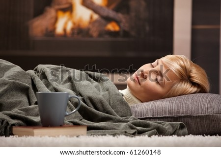 Woman sleeping at home lying on floor in front of a fire place, - stock photo