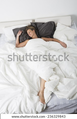 Woman sleeping in a white bedroom environment from high angle view - stock photo