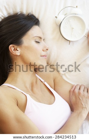 Woman Sleeping In Bed With Alarm Clock - stock photo