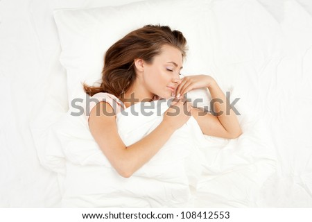 Woman sleeping in her bed - stock photo