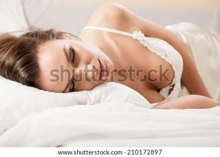 Woman sleeping in sexy underwear in bed - stock photo
