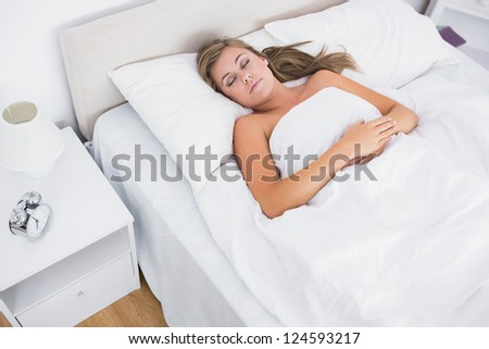 Woman sleeping in white bedroom during the day - stock photo