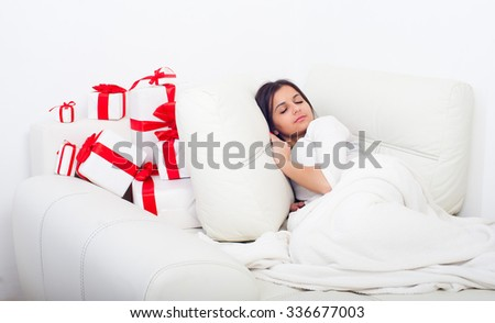 Woman sleeping on the bed with presents standing near her. Focus on gift - stock photo