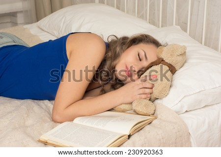 Woman sleeping on the bed/Woman sleeping on the bed with a book and a teddy bear - stock photo