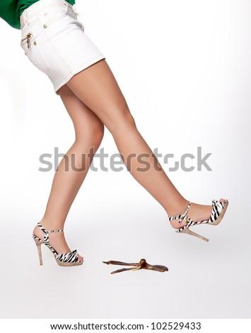Woman slips on a banana peel - stock photo