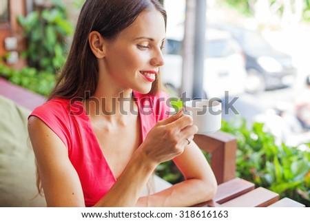 woman slowly drinking and enjoying her morning cup of coffee - stock photo