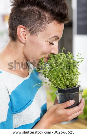 Woman smelling on a plant of fresh thyme. She is holding the plant in her hands.  - stock photo