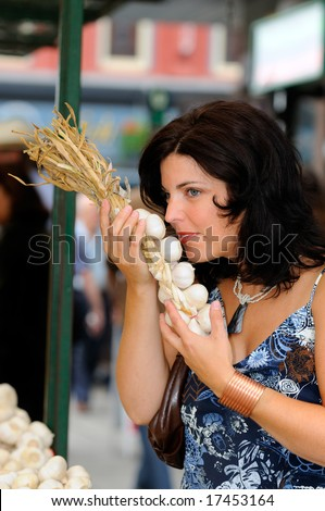 Woman Smelling Organic Garlic At A Farmers Market - stock photo