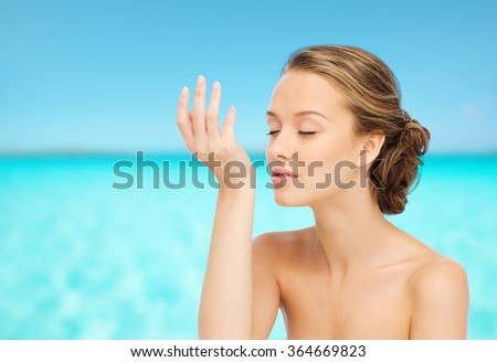 woman smelling perfume from wrist of her hand - stock photo