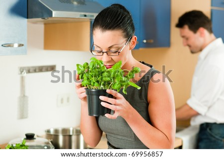 Woman smells the aroma of a basil pot in her kitchen a in the background her husband is cooking - stock photo