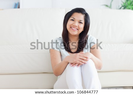 Woman smiles as she sits on the floor in a living room in a living room - stock photo