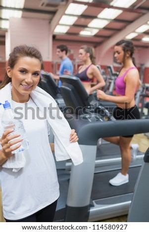 Woman smiling and drinking a bottle of water in the gym after exercise - stock photo