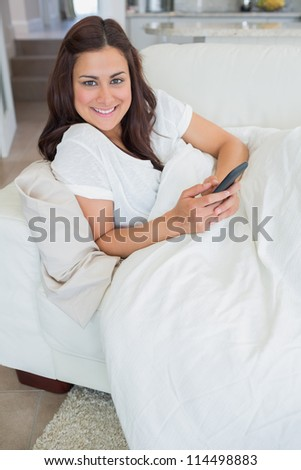 Woman smiling and holding a mobile phone while relaxing - stock photo