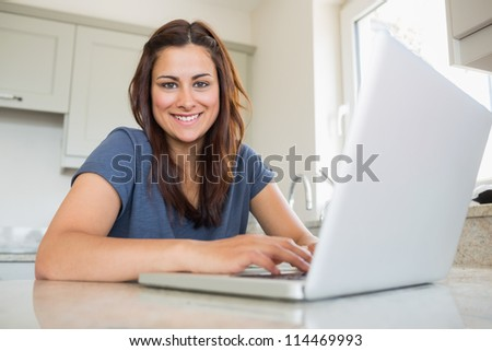 Woman smiling and using laptop in kitchen - stock photo