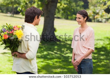 Woman smiling as she greets her friend who is holding flowers behind his back - stock photo