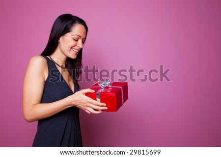 Woman smiling as she receives a present wrapped in red wrapping paper with silver ribbon and gift bow. - stock photo