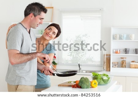 Woman smiling at her husband in a kitchen - stock photo