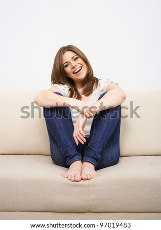 woman smiling isolated with sofa - stock photo