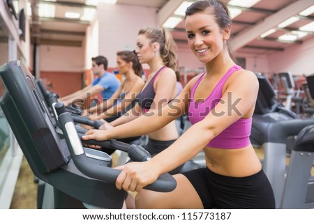 Woman smiling on exercise bicycle in the gym - stock photo