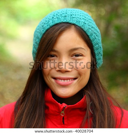 Woman smiling outdoors in Autumn. Beautiful mixed asian / caucasian woman walking in the forest on a fall day. - stock photo