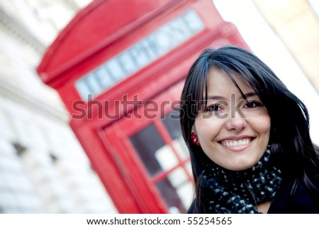 Woman smiling outside a telephone booth in London - stock photo