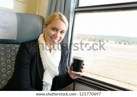 Woman smiling sitting in train holding coffee commuter travel confident - stock photo