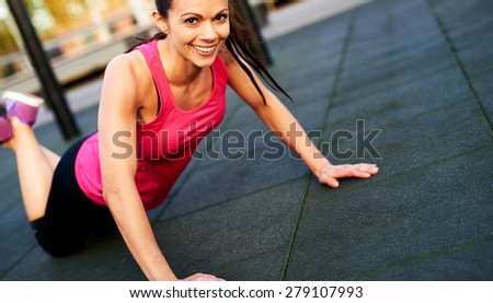 Woman smiling while doing a modified push up  outside. - stock photo