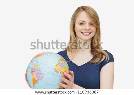 Woman smiling while holding a globe against a white background - stock photo