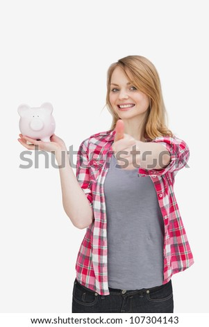 Woman smiling while holding a piggy bank against a white background - stock photo