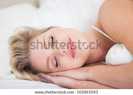 Woman smiling while she is resting on her bed - stock photo