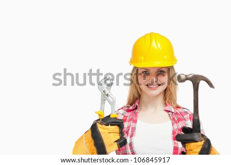 Woman smiling while wearing a safety helmet against white background - stock photo