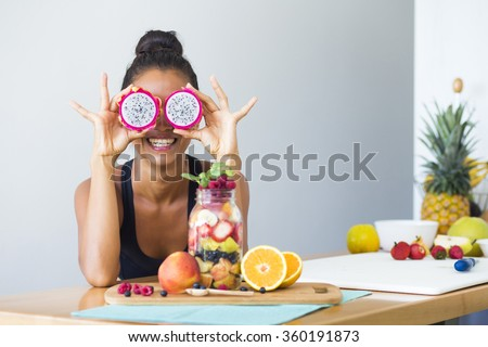 Woman smiling with a tropical fruit salad, being playful covering her eyes with dragon fruit - stock photo