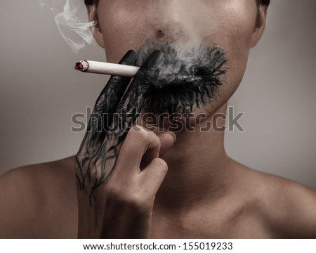 Woman smokes a cigarette, her hand and her mouth blackened, concept of a slow death from smoking - stock photo