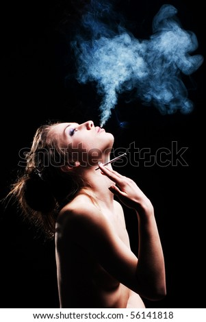 woman smokes in the dark - stock photo
