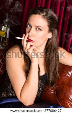 Woman smoking cigarette in a lounge - stock photo