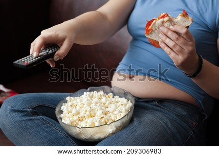 Woman snacking and zapping. - stock photo