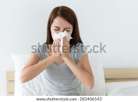 Woman sneeze on bed - stock photo