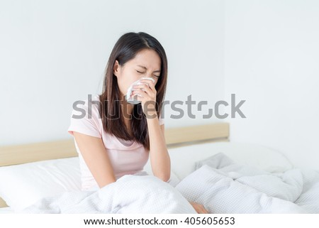 Woman sneezing on bed - stock photo