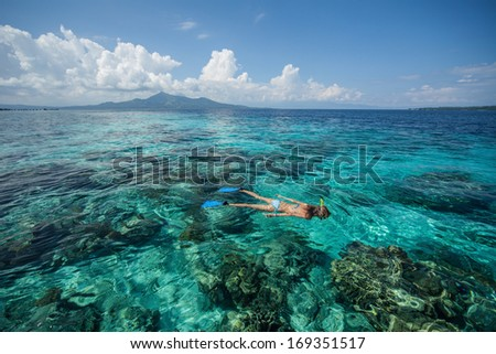 Woman snorkeling in a tropical sea over coral reef. Indonesia - stock photo