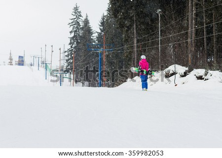 Woman snowboarder on the slopes frosty winter day. Beautiful girl on snoborde in the snow. - stock photo