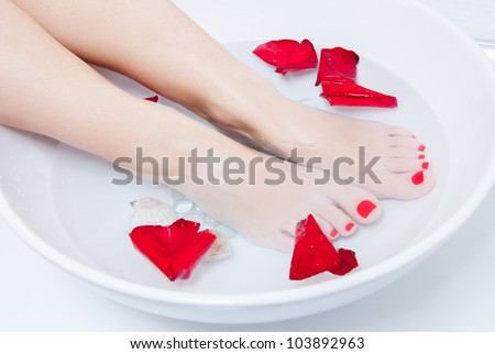 woman spa pedicure foot treatment with water and flower - stock photo