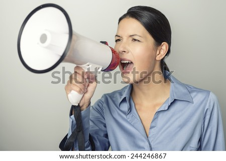 Woman speaking over a megaphone as she makes a public address, participates in a protest or organises a rally or promotion, over grey with copyspace to the side - stock photo
