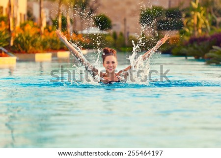 woman splashing a water at swimming pool - stock photo
