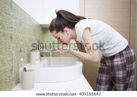 Woman splashing face with water above bathroom sink - stock photo