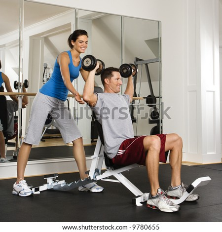 Woman spotting man lifting weights at gym. - stock photo